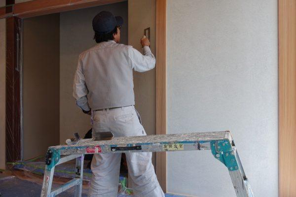 室内壁に珪藻土仕上げを施工しているベテラン職人Fさん、手前は足場