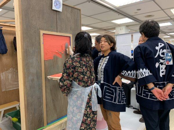 塗り壁体験をする女性、先生は原田左官梅田ひかり。ものづくり匠の技の祭典左官ブース