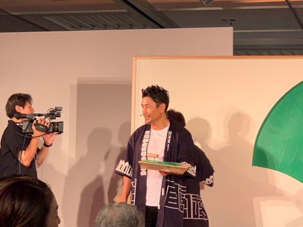 鏝板を持った魔娑斗さん、東京都左官組合連合会の法被を着ている。ものづくり匠の技の祭典の左官ライブにて