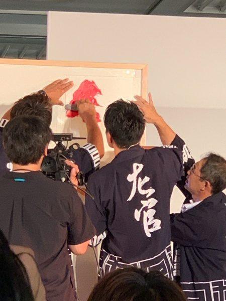 左官の文字の型をあてた上から赤い珪藻土を塗っている。ものづくり匠の技の祭典の左官ライブ