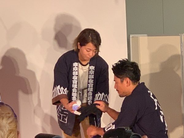 魔娑斗さんに原田左官の梅田さんが道具を渡している場面。ものづくり匠の技の祭典の左官ライブにて