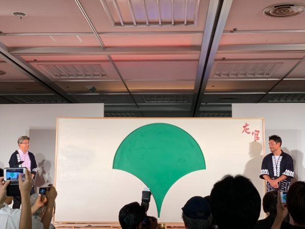 緑色の珪藻土で塗った東京都シンボルマークと赤色の珪藻土で塗った左官の文字、周りを白い漆喰で塗った壁。施工した魔娑斗さんと左官組合のかたが並んでいる。ものづくり匠の技の祭典の左官ライブ