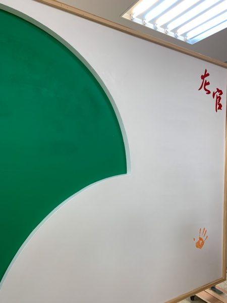 ものづくり匠の技の祭典で作成された左官パネル、緑色の珪藻土と赤色の珪藻土と白い漆喰で塗ってある。手形がある。