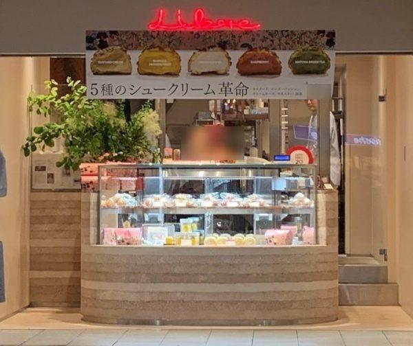 パティスリーリーブル福岡天神店、塗り版築のディスプレイカウンター、カウンターにはシュークリーム等商品が並んでいる