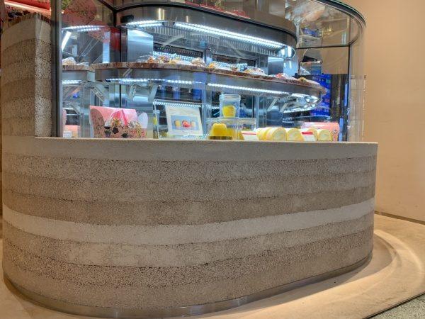 塗り版築のディスプレイカウンター、カウンターには商品が並んでいる。パティスリーリーブル福岡天神店