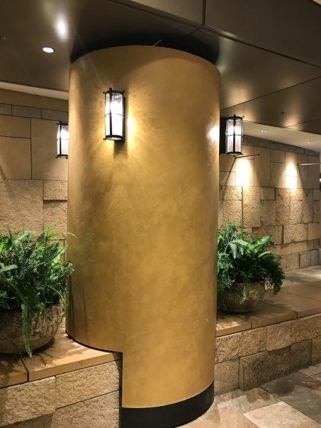 暖色系のオルトレマテリアで施工した商業施設の円柱、円柱は照明付き、周りには観葉植物や照明がある