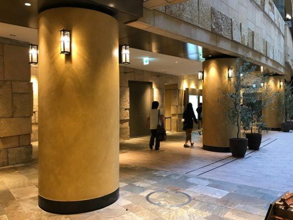 暖色系のオルトレマテリアで施工した商業施設の円柱、円柱は照明付き、三本の円柱がある、商業施設のお客さんが数名歩いている
