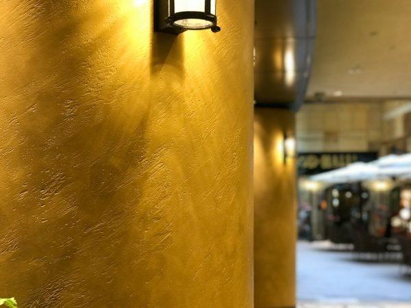 暖色系のオルトレマテリアで施工した商業施設の円柱、円柱は照明付き、手前と奥に円柱が2本、
