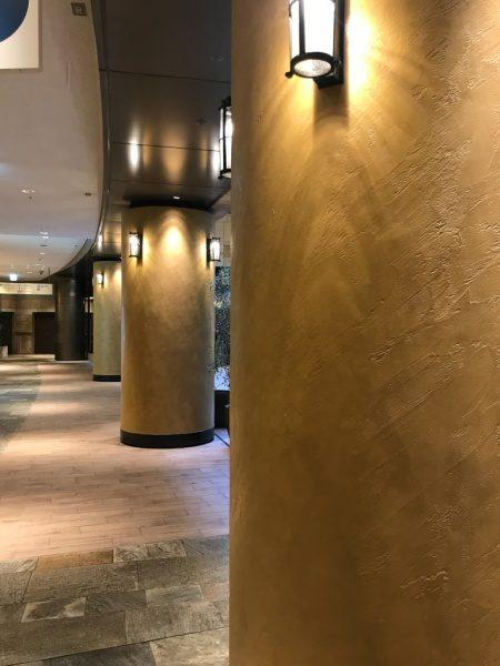 暖色系のオルトレマテリアで施工した商業施設の円柱、円柱は照明付き、円柱が4本映っている