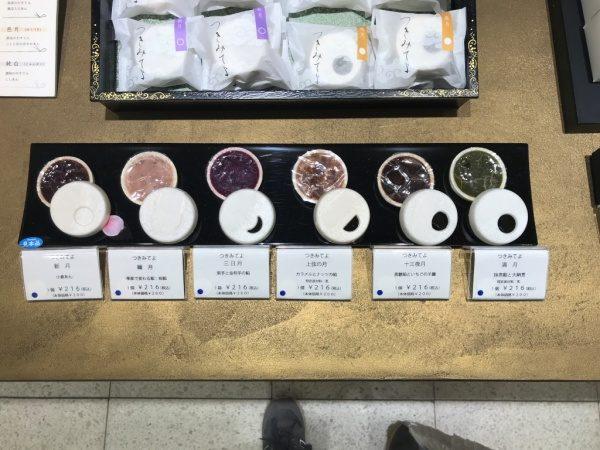 金色のオルトレマテリアで施工されたディスプレイ用カウンターテーブル、巌邑堂日本橋高島屋店、商品の和菓子が手前に6種類と奥に4個ある