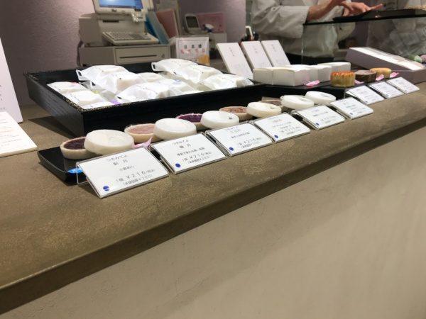 金色のオルトレマテリアで施工されたディスプレイ用カウンターテーブル、巌邑堂日本橋高島屋店、商品の和菓子が並んでおり奥にはレジ、お店の従業員の手元が映っている