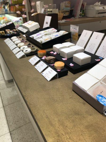 金色のオルトレマテリアで施工されたディスプレイ用カウンターテーブル、巌邑堂日本橋高島屋店、商品の和菓子が様々な種類で沢山ある