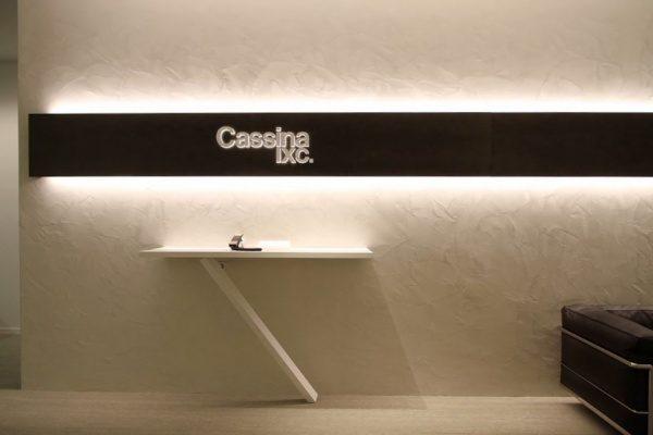 白いオルトレマテリアで施工された壁、カッシーナ・イクスシー青山オフィスエントランス、テーブルがあり壁には社名ロゴ