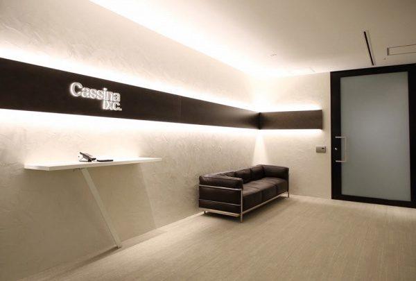 白いオルトレマテリアで施工された壁、カッシーナ・イクスシー青山オフィスエントランス、テーブルがあり壁には社名ロゴ、黒いソファやドアがある