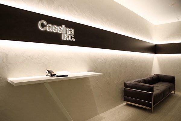 白いオルトレマテリアで施工された壁、カッシーナ・イクスシー青山オフィスエントランス、テーブルがあり壁には社名ロゴ、黒いソファがある