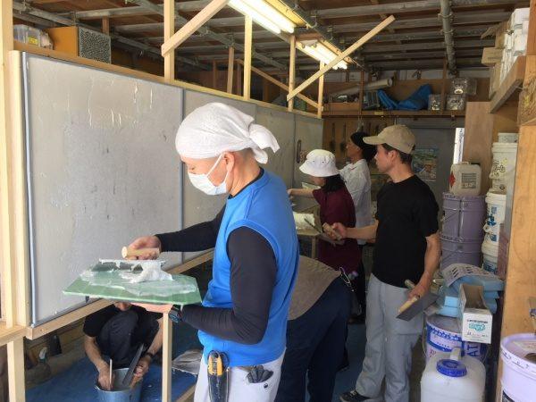 原田左官社内講習。数人が枠の壁に鏝で材料を塗りつけている