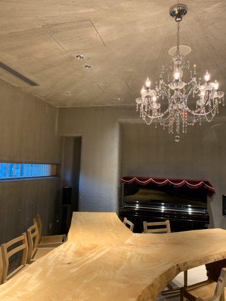 特殊モルタル仕上げで洞窟風の内装の壁と天井。机と椅子やシャンデリアやピアノがある。銀座小松庵の特別室