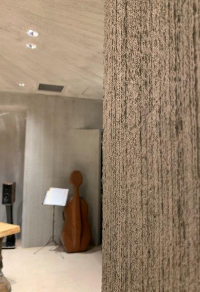 特殊モルタル仕上げの壁。奥には弦楽器と譜面台やスピーカーがある。銀座小松庵の特別室