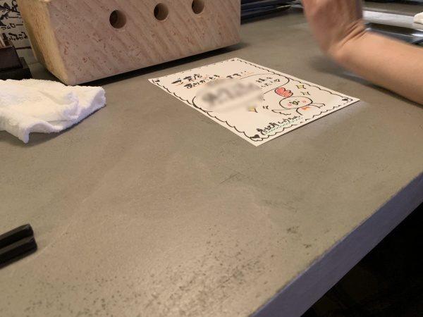 モールテックスグレーのカウンターテーブル。恵比寿の飲食店。挨拶カードがある