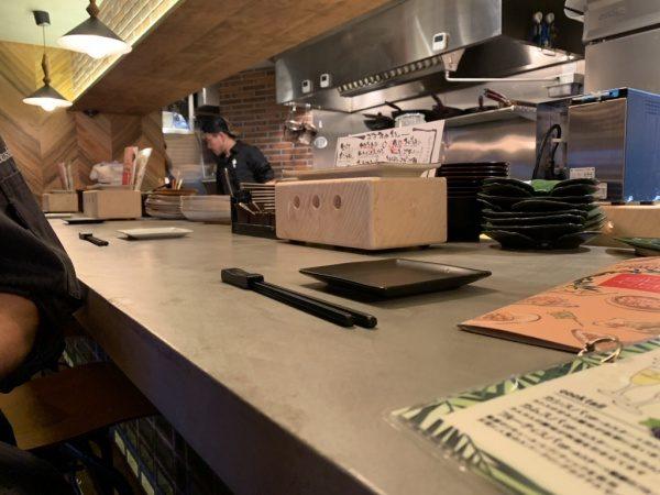 モールテックスグレーのカウンターテーブル、お皿やお箸やメニューなどがある。恵比寿の飲食店。