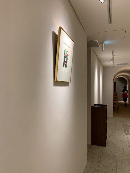 樹脂系左官材による漆喰調仕上げで施工した内壁。絵画がかかっている。小松庵銀座店
