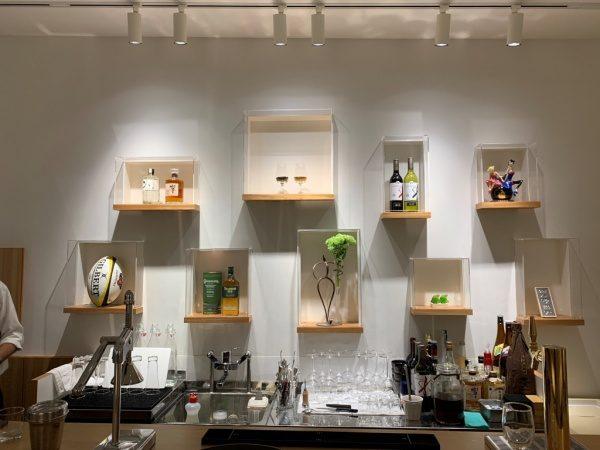 樹脂系左官材による漆喰調仕上げで施工した内壁。棚にお酒のボトルや花などが飾ってあり、下のキッチン台にグラスやボトルなど様々な物がある。小松庵銀座店