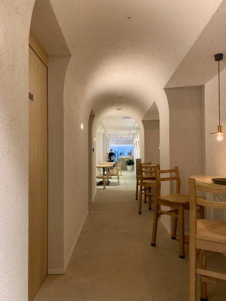 藁入仕上げの白色の壁。椅子が並んでいる。小松庵銀座店の廊下