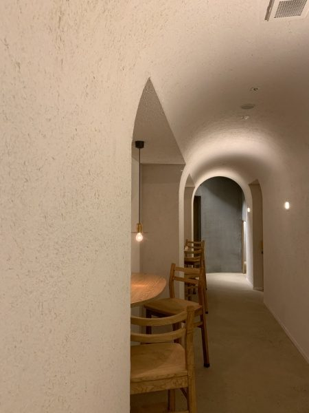 藁入仕上げの白色の壁。掘り込み箇所に机や椅子がある。小松庵銀座店の廊下