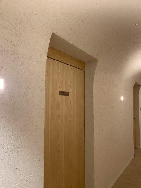 藁入仕上げの白色の壁。掘り込みや扉の部分の壁面もRを付けている。小松庵銀座店の廊下