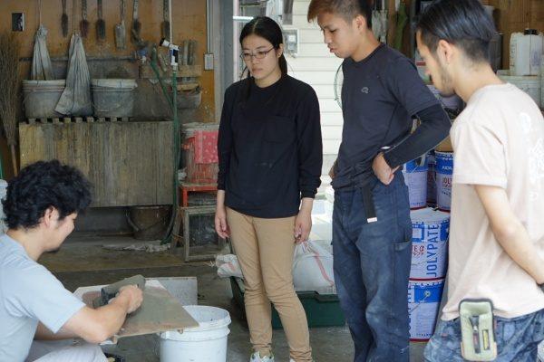 原田左官新人研修、鏝板の上の材料を鏝で触っている講師役の職人さんとそれを見る3名の新入生さん