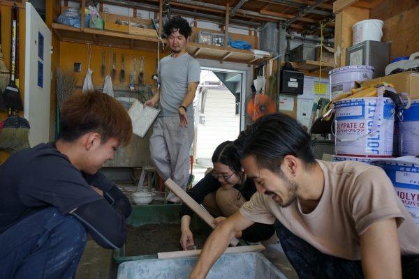 原田左官新人研修、モルタル施工の疑似体験をする3名の新入生さんと後ろで指導する職人さん