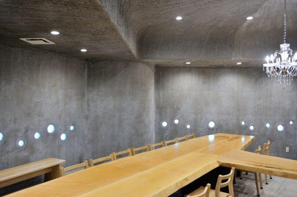 モルタル特殊仕上げの壁面と天井。テーブルと椅子がある。お蕎麦屋さん「小松庵 総本家」