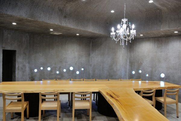 モルタル特殊仕上げの壁面と天井、刷毛引きと鏝模様で仕上げています。周りにテーブルや椅子がある。お蕎麦屋さん「小松庵 総本家」