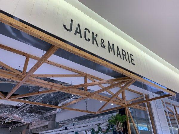 うづくり木目モルタルの施工例。お店の上部のロゴ部分、うづくりは縦張りで色は白色