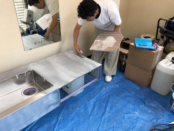 キッチンシンクに下塗りのフォンドフレックスを施工中の職人さん