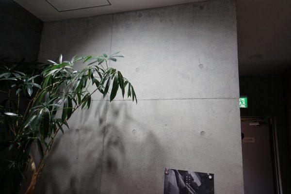 昼光色の照明に照らされているコンクリート打ち放し風仕上げの壁。原田左官ショールーム