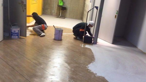 施工店舗の床に特殊なモルタルを塗っている