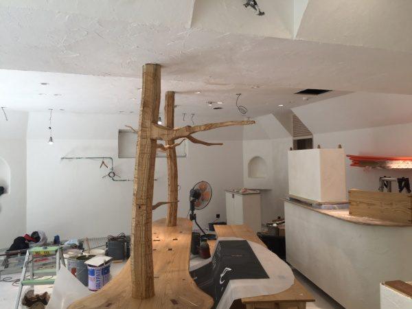 秋葉原マザーハウスe.。原田左官漆喰施工。内装が仕上がってきた状態で栗の木がある