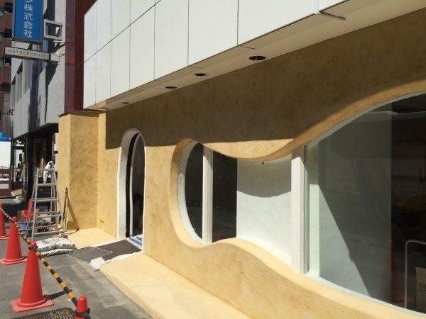秋葉原マザーハウスe.。原田左官カラーモルタル外壁施工。店舗外壁の窓枠と入り口周り箇所、入り口のR部分を漆喰で縁取り