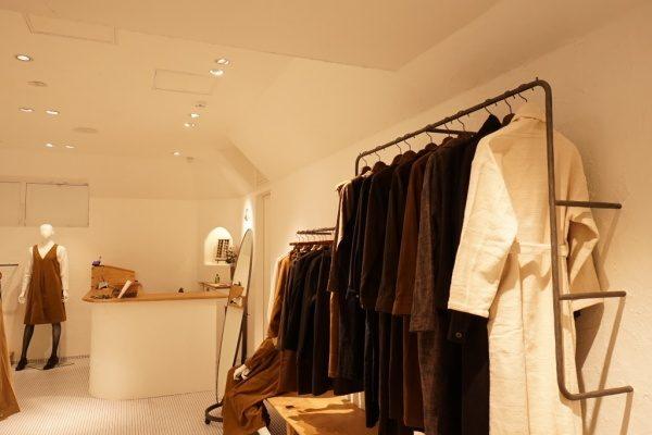 秋葉原マザーハウスe.。原田左官漆喰施工。完成した店舗内装、ハンガー掛けにはお店のお洋服が掛かっている