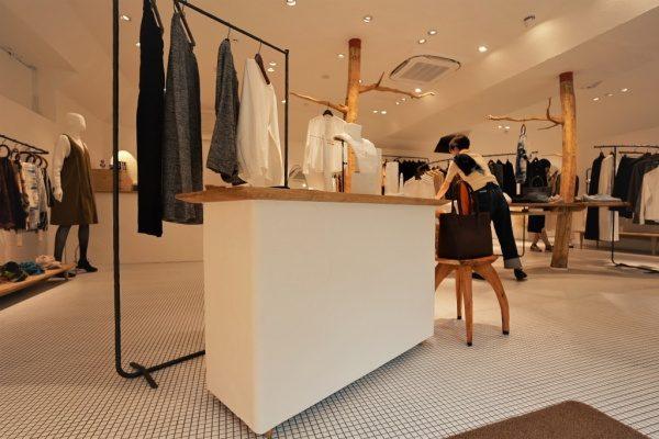秋葉原マザーハウスe.。原田左官漆喰施工。完成した店舗内装、什器箇所。その周りには店員さんが居てお洋服が沢山ある