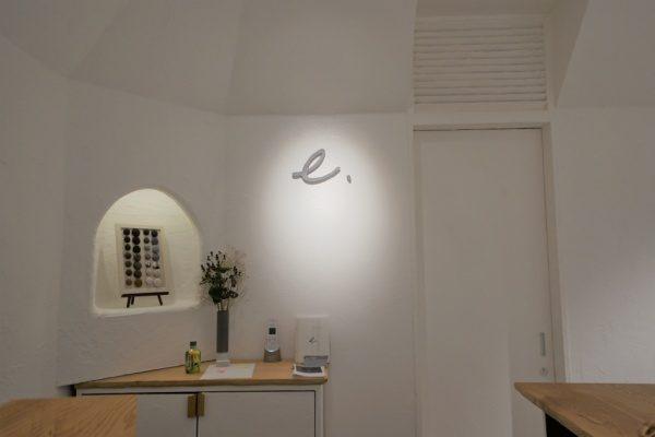 秋葉原マザーハウスe.。原田左官漆喰施工。完成した店舗内装、ロゴに照明があたっている