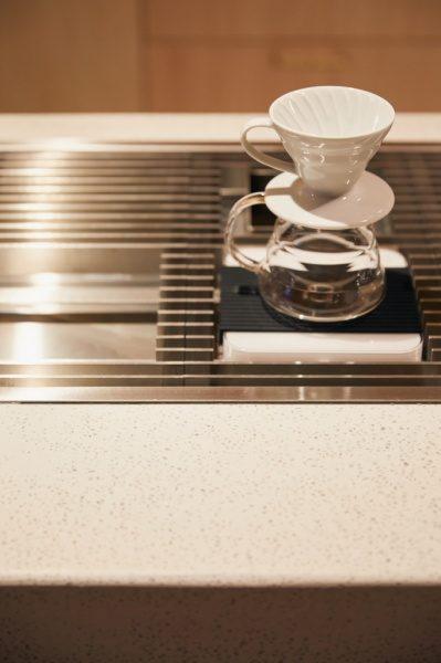 セメント研ぎ出しのカフェカウンター。コーヒー専用の特注ストーブとコーヒカップ