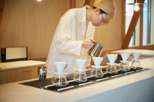 セメント研ぎ出しのカフェカウンター。店員さんがコーヒーを淹れている