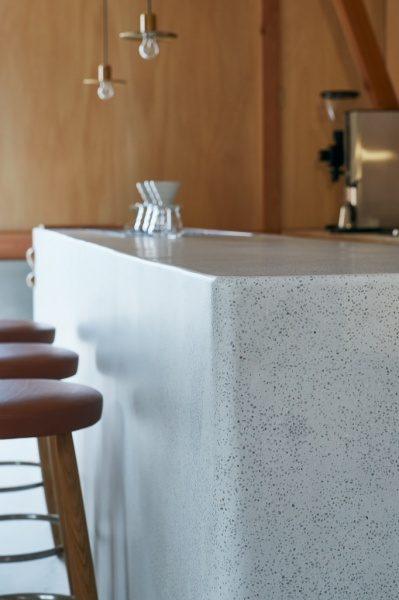 セメント研ぎ出しのカフェカウンター。椅子の影がうっすら反射している