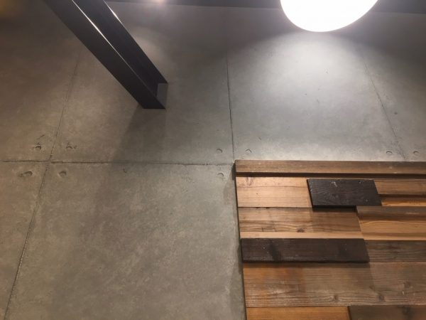 コンクリート打ち放し風仕上げをカフェの壁面に施工。石膏ボードの上から仕上げている