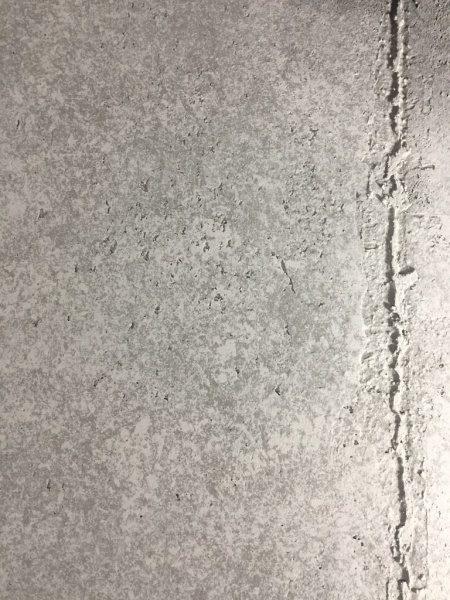 コンクリート打ち放し風仕上げの壁。神宮前のジュエリーショップコアジュエルスに施工。コンクリートのダメージ感を手作業で出してある