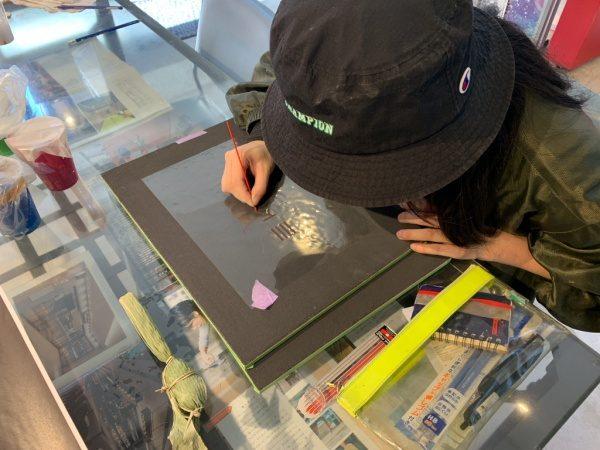 黒の珪藻土に型抜きされた透明なシートを張り、色付けの滲み対策で外周をなぞっている