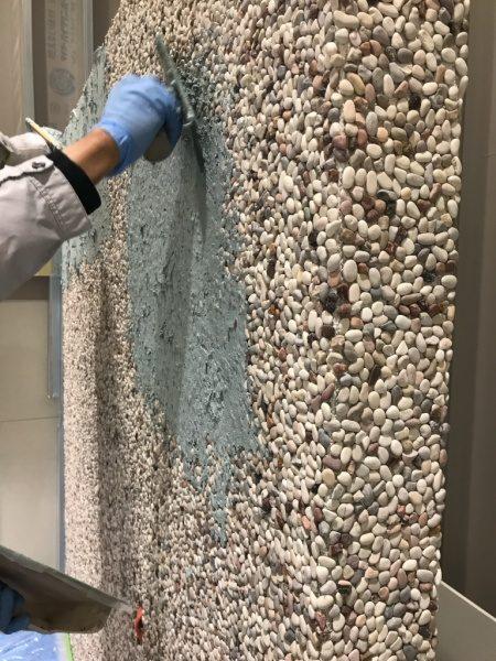 玉石洗い出しシートの壁にお茶の葉入りビールストーン塗付け施工中