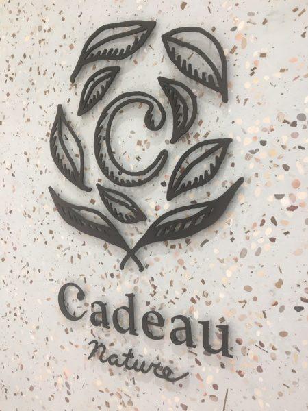 お茶の葉入り玉石ビールストーンの壁。渋谷カドーナチュール壁面ロゴ
